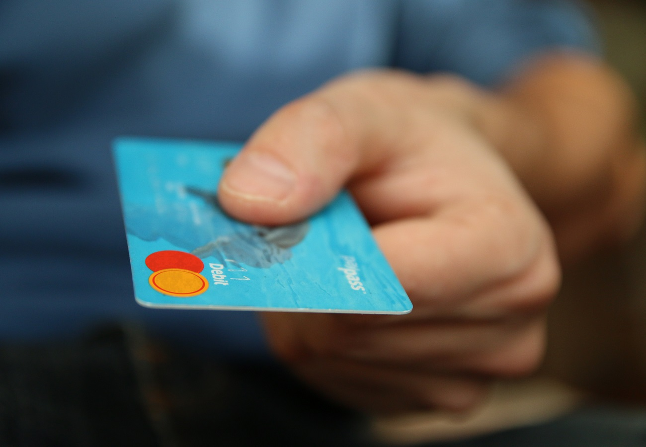 person holding credi card in hand- safety while shopping online